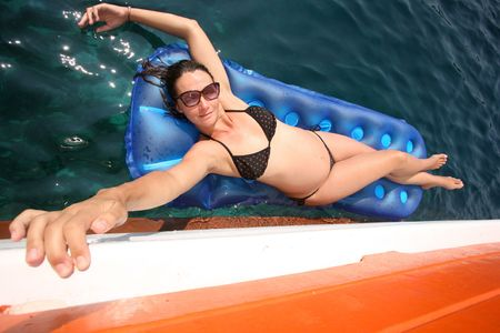 Woman enjoying her summer on a lilo on the sea photo