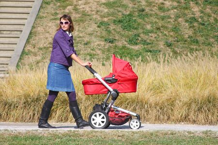 Young mother pushing pram in park on sunny day photo