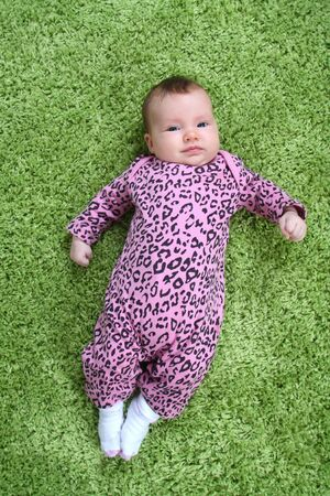 baby laying on his back on green carpet in pink leopard outfit photo