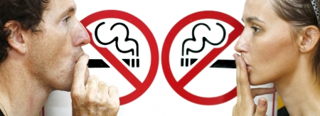 man smoking: couple smoking a no smoking sign