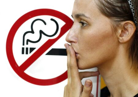 quit: Lady smoking a non-smoking panel Stock Photo