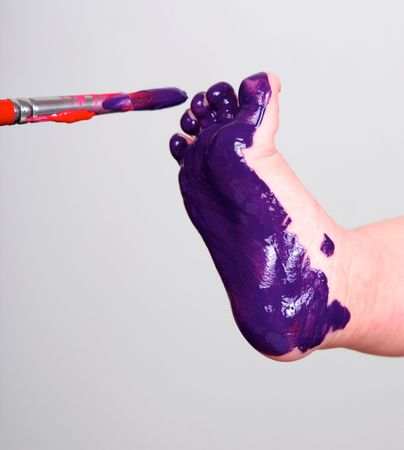 painting a babyfoot purple with a brush Stock Photo - 6043290