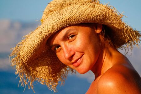 a portrait of a young woman with a straw hat on the beach photo