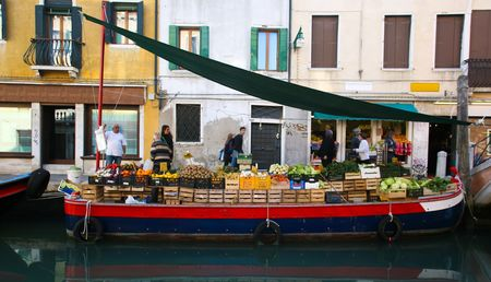 local business: VENICE - OCT 28. Fruit and vegetable stall on boat on canal on October 28, 2009 in Venice, Italy. The population of Venice decreases yearly making local business increasingly difficult. Stock Photo