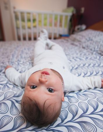 Cute baby laying on back on pattern bedspread photo