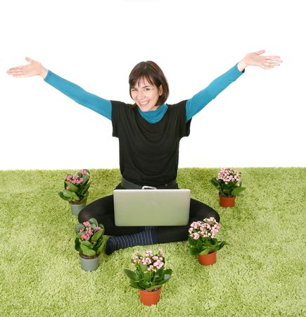 Happy woman with laptop and flowers on green rug Stock Photo - 6668575