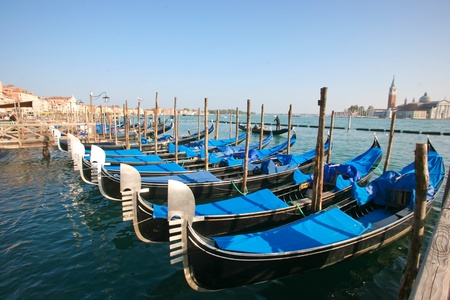 Group of gondolas docked on the water in Venice, Italy photo