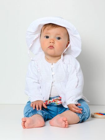 7 month old baby sitting with hat dressed in jeans and jumper photo