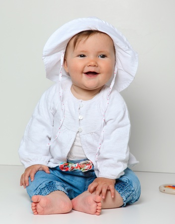 7 month old baby sitting with toy dressed in jeans and jumper Stock Photo - 8941091