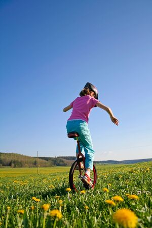 young girl in field riding her monocycle photo