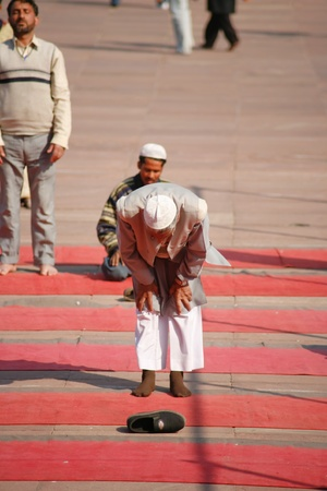 bowed head: DEHLI - FEBRUARY 11. Muslim men praying on pilgrimage to Jama Masjid mosque on February 11, 2008 in Dehli, India. Its the largest mosque in India with millions of visitors each year.