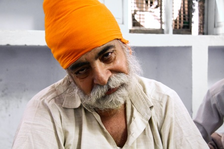 DELHI - SEPTEMBER 22:  Old bearded Sikh with orange turban at Sis Ganj Gurdwara temple  on September 22, 2007 in Delhi, India. Worldwide there are about 25 million Sikhs.