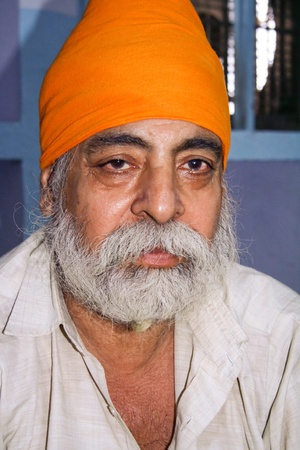 gurdwara: DELHI - SEPTEMBER 22:  Old Sikh devotee with orange turban at Sis Ganj Gurdwara temple  on September 22, 2007 in Delhi, India. Worldwide there are about 25 million Sikhs.