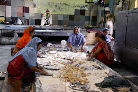 delhi: DELHI - SEPTEMBER 22:  Women preparing food in Sikh temple kitchen on September 22, 2007 in Delhi, India. Sikh temples can serve thousands of free meals everyday.