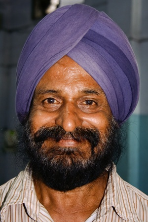 gurudwara: DELHI - SEPTEMBER 22:  Sikh man with purple turban at Sis Ganj Gurdwara on September 22, 2007 in Delhi, India. Worldwide there are about 25 million Sikhs.