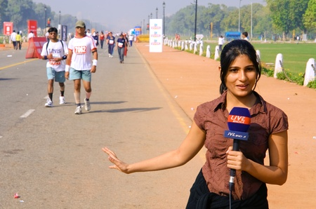 commentator: DELHI - October 28: Young female TV commentator reporting on marathon on October 28th, 2007 in Delhi, India.