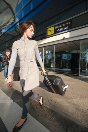 Young business woman at airport with luggage Stok Fotoğraf