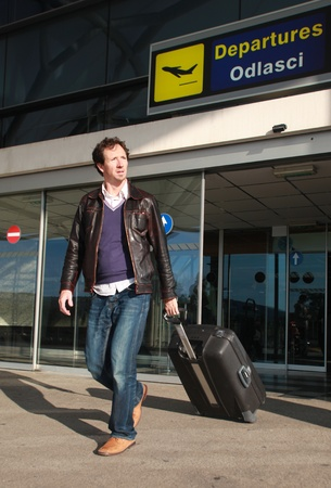 Young casual business business traveller exiting airport photo