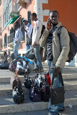the merchant of venice: VENICE - OCTOBER 26: African street hawkers with fake leather bags on October 26, 2009 in Venice. Most African vendors are illegal and create tough competition for local businesses