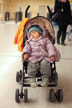 buggy: Exhausted young child sleeping in pram Stock Photo