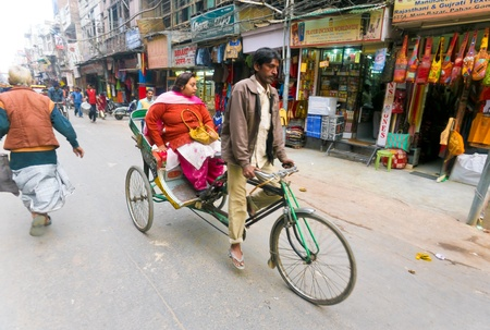 DELHI - JANUARY 15: Man driving female passenger on a cycle rickshaw through city area on January 15, 2008 in Delhi, India. This is the cheapest means of transport when youre in no rush. Stok Fotoğraf