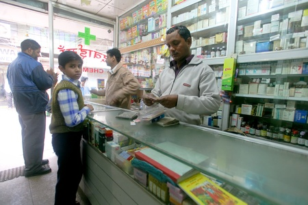 DELHI - FEBRUARY 2008. Pharmacy assistant selling medicine to customers on February 12, 2008 in Delhi, India. 80% of medicine revenue comes from international markets and just 20% from India. Publikacyjne
