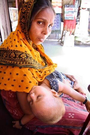 beggar: woman beggar with her baby delhi india