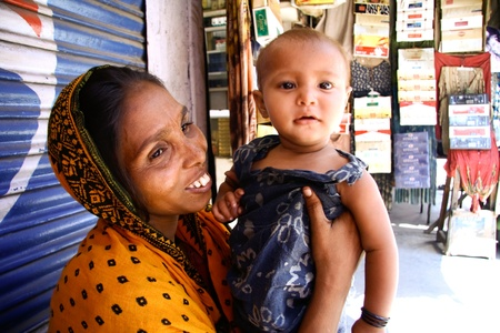 slum: DELHI - SEPTEMBER 22: Young female beggar with child on September 22, 2007 in Delhi, India. Begging is a profession for many women in Pahar Ganj.