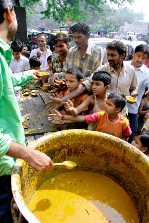 DELHI - OCTOBER 20: Men and children getting a free meal on October 20, 2007 in Delhi, India. To be on Gods good side, some hindu faithfuls organise free food for the poor. Editöryel