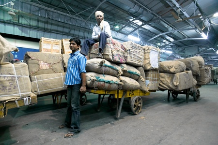 DELHI - FEBRUARY 19: Men moving cargo onto train by trailer on February 19, 2008 in Delhi, India. Indian railways transports more than 2 million tonnes of freight daily.