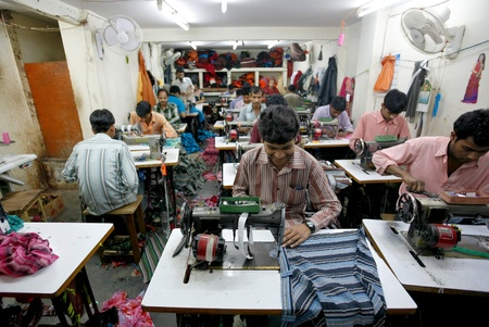 INDIA - FEB 26: Textile workers in a small factory in Old Delh on February 26, 2008 in Delhi, India. Many small factories provide the West with their clothes. Editöryel