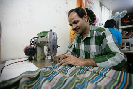 INDIA - FEB 26: Textile worker in a small factory in Old Delh on February 26, 2008 in Delhi, India. Many small factories provide the West with their clothes.