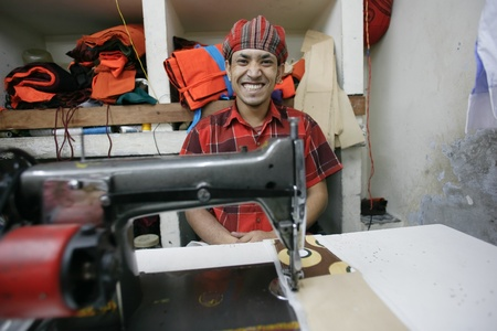 underpaid: INDIA - FEB 26: Smiling textile worker in a small factory in Old Delh on February 26, 2008 in Delhi, India. Many small factories provide the West with their clothes.