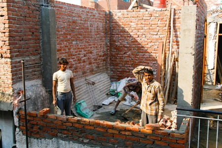DELHI - FEBRUARY 29: Three men laying a brick wall for a house on February 29, 2008. Contributing to Indias booming economy.