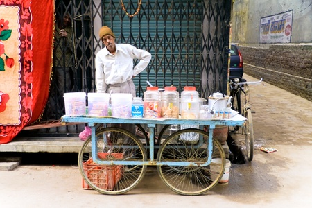 street vendor: DELHI - DECEMBER 2: Mobile tea stall merchant selling sweets, biscuits and drinks on December 2, 2007 in Delhi, India. It is local tradition to drink tea from the street.