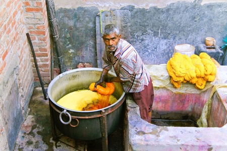 DELHI - DECEMBER 2: Worker dyeing fabric with pot of orange dye on December 2, 2007 in Delhi, India. Most traditional dyeing is done by hand.