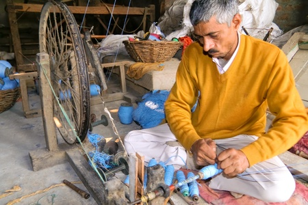 DELHI - DECEMBER 2: Middle-aged man in workshop threading cotton spools on December 2, 2007 in Delhi, India. Most traditional fabrics are made by hand. Editöryel