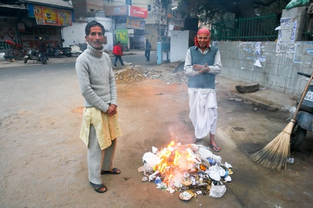 Two men burning rubbish on the street creating CO2 emissions on January 18, 2008 in Delhi, India. With no rubbish disposal service, locals burn their litter.
