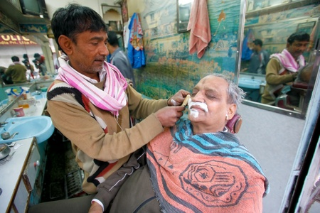DELHI - JANUARY 18: Barber shaving a customer in shop interior on January 18, 2008 in Delhi, India. For only 20c you can have a face massage and a shave. Stock Photo - 8945339