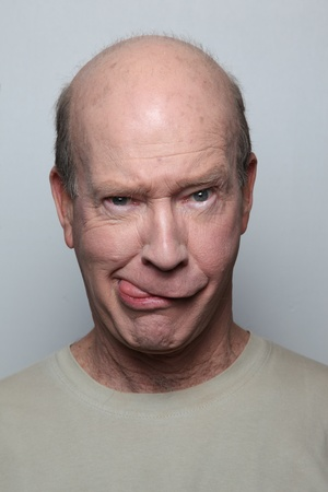Man making funny face sticking out tongue photo