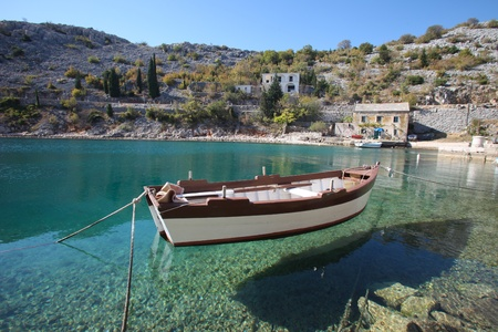 View of old stone house with a wooden boat moored in little bay photo