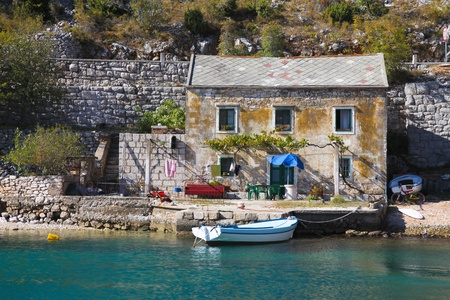 mediterranean home: View of old stone house with a wooden boat moored in little bay Editorial