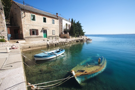 sunk: View of old stone house with a wooden boat sunk in little bay