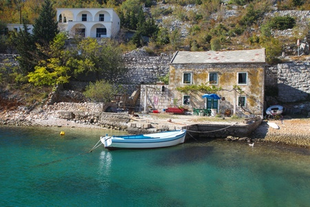 View of old stone house with a wooden boat moored in little bay Stock Photo - 10868004