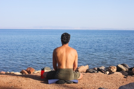 Man meditating on the shores of the red sea in Egypt photo