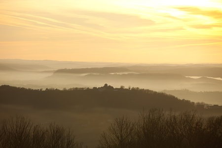 Misty hills and village silhouette in the French countryside in Correze. photo
