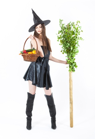beautiful eco witch with a broomstick and vegetable basket photo