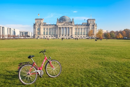 quarterly: BERLIN - NOVEMBER 3, 2011: Red bike infront of green area of Bundestag on November 3, 2011 in Berlin, Germany. This landmark is the most visited attraction in Berlin. Editorial