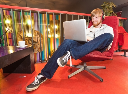 Young man on laptop sitting in lounge photo