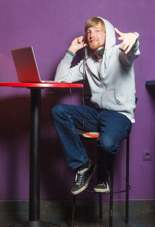 Cool young man with hoodie sitting working on laptop in cool location photo